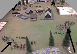 The Norman warlord rushes into the village to rescue his lady. The two Viking bands, wary of each other, approach the village. The Saxons hide in the trees.