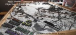 Before deploying the Russian forces, the players plan their attack. The main objective is the fortified artillery position at the end of the table. Cutting the road to the right is a secondary objective.